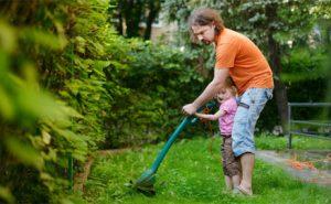 dziecko z tata kosi trawe